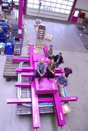 Pink steel and concrete weights reproduce the force of the relative movements that the 85 ITER bellows will have to withstand during operation of the Tokamak. Adding their weight to the ensemble: Igor Sekachev and Guillaume Vitupier (ITER Organization), Girish Kumar Gupta and Anil Bhardwaj (ITER India), and Werner Löhrer and Reto Löhrer (Kompaflex AG). (Click to view larger version...)