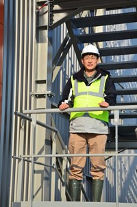 Byung Su Lim, leader of ITER's Poloidal Field Coil Section, posing in front of the completed winding facility. (Click to view larger version...)