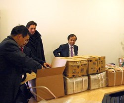 The book donor Luo Delong (right) looking at the precious goods that have just arrived from China. (Click to view larger version...)