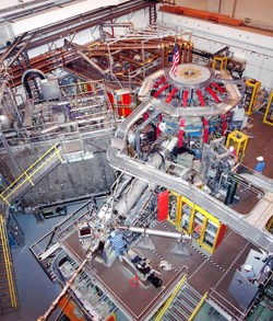 Inside the NSTX test cell: the apple-shaped fusion experiment includes exterior vertical red magnetic coils and horizontal blue magnetic coils. The rectangular steel box to the left of the machine contains the neutral beam system for heating plasma. (Click to view larger version...)