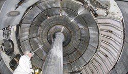 A researcher takes an upward view of the interior of NSTX, shown with the centre column. Copyright for all three photos: Princeton Plasma Physics Lab. (Click to view larger version...)
