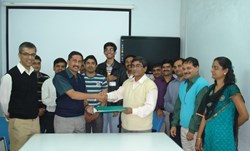 Shishir Deshpande (centre left) handing over the signed document to Biswanath Sakar from the ITER India project team... (Click to view larger version...)
