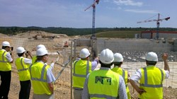 Under the sun of Provence, the delegation looks toward the Tokamak's anti-seismic ''pillows'' and listens to Tim Watson (pointing), director for Buildings & Site Infrastructure, as he relates the latest on ITER construction. (Click to view larger version...)