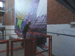 A SCK•CEN staff member installing the stainless steel tube to the poster. (Click to view larger version...)