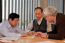 Kijung Jung (left) working on a document with Japanese colleagues Hideo Nakajima and Kiyoshi Okuno. (Click to view larger version...)