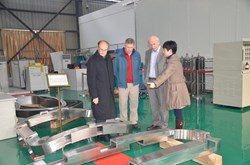 Wei Jing, team leader at ASIPP for the correction coils, showing model cases to Michel Huguet and, from the ITER Organization, Mark Gardner and Adamo Laurenti. One bottom correction coil model case and one side correction coil model case are visible. (Both are of reduced overall size but with full-size cross section.) (Click to view larger version...)