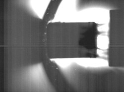 A 16 mm neon—deuterium pellet, indicated by an arrow, captured with a high speed camera as it travels from left to right at about 300 metres per second in a test stand at the Oak Ridge National Laboratory Pellet Lab. Photo: ORNL (Click to view larger version...)