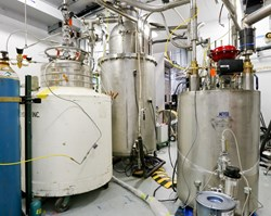 A view of the test environment at the Spallation Neutron Source shows a white tank containing helium on the left, the prototype cryoviscous compressor pump in the middle, and the valve box, which monitors the flow rate to the pump, on the right. Photo: US ITER/ORNL (Click to view larger version...)