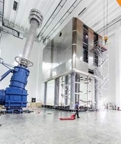 Standing on eight legs, six metres overhead, the high-voltage deck of the MITICA testbed is an electrically insulated box that hosts the power supplies for the neutral beam injector's ion source. © Consorzio RFX (Click to view larger version...)