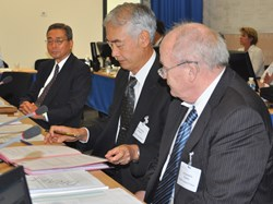Kaname Ikeda looks on as Council Chair Evgeny Velikhov presents professor Osamu Motojima with his ITER contract. (Click to view larger version...)