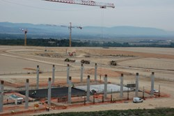 The columns for the Poloidal Field Coil Winding Facility are rising out the ground in the foreground, while the Tokamak Pit is taking shape in the background. (Click to view larger version...)