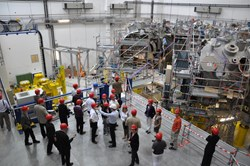 IPP spokesman Robert Wolf showing the group around the Wendelstein W7-X assembly hall. Photo: Ralph Schorn (Click to view larger version...)