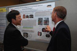 Jiangang Li (left), an eloquent promoter of fusion energy, discussing a poster at last week's SOFE. (Click to view larger version...)