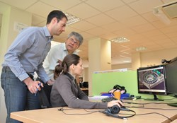 Fabien Berruyer, Design Coordinator (DECO) of the Cooling Water System and Eric Martin, Head of the ITER Design Office, look on as CAD designer Andreea Rîşnoveanu is busy working on a component. (Click to view larger version...)