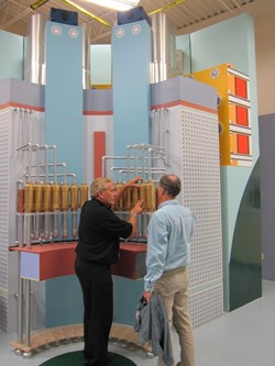 In this wooden engineering mock-up, module 3L is seen in crosssection, the upper part of the toroidal field coils is represented at the back with the precompression ring fixture in orange, and the vertical tie-plates (part of the central solenoid precompression structure) are represented in light blue. Charles Lyraud and Neil Mitchell from the ITER Organization talk over insulating breaks. (Click to view larger version...)