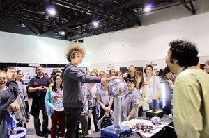 Arturo Dominguez, a postdoctoral fellow in PPPL's Science Education department, and a group of students watch a student's hair stand on end in a static electricity demonstration. © Princeton Plasma Physics Laboratory (Click to view larger version...)