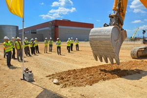 A large excavator symbolically scratched the earth where the 26-metre-high, 110-metre-long Cryostat Workshop will soon be erected. (Click to view larger version...)