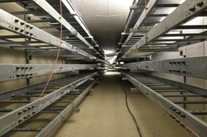 Cable trays line the two sides of the electrical service tunnel like bunk beds. ''You could walk these tunnels from the cooling towers on the east side of the worksite to just outside the grid yard on the west side,'' says Laurent Schmieder. (Click to view larger version...)