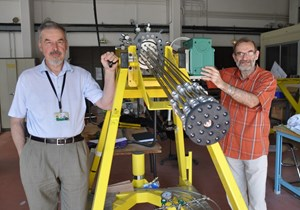 Sergei Putvinski (left) and fusion physicist François Saint-Laurent (IRFM) are not manning a Gatling machine gun. They stand next to the prototype DMS gun cartridge that will run its first tests at the end of the month. (Click to view larger version...)