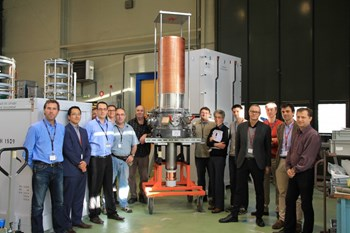 Representatives from the European Domestic Agency, the European Gyrotron Consortium, and Thales Electron Devices stand next to the continuous-wave gyrotron prototype, which has successfully passed final factory acceptance tests. (Click to view larger version...)