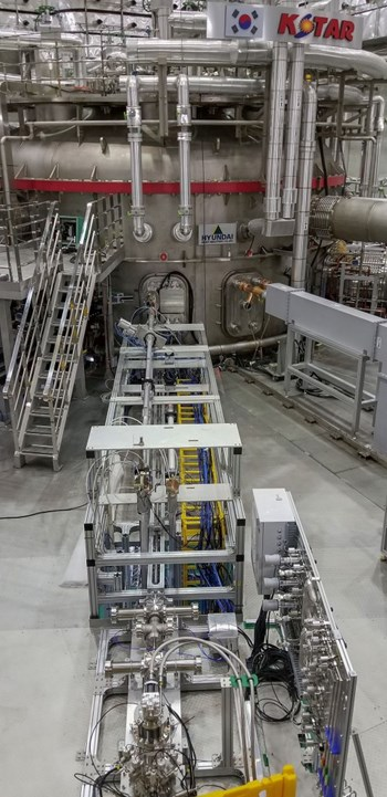 One of the two injectors at KSTAR—the pellets are formed in the cryogenic chamber visible in the foreground and are then injected into the plasma through a flight tube of more than 10 m in length. The gas distribution panel is visible on the right. Vacuum components also ensure that propellant gas that is used to release and accelerate the pellets is held back to not enter the plasma before the pellet. A microwave cavity measures the velocity and mass of the injected pellet. (Click to view larger version...)