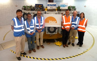 At a newly created facility at CNIM, representatives of ITER, the European Domestic Agency, manufacturer Douce Hydro and host CNIM stand before the test bench where nine pre-compression rings will be tested (three upper, three lower and three spare). (Click to view larger version...)