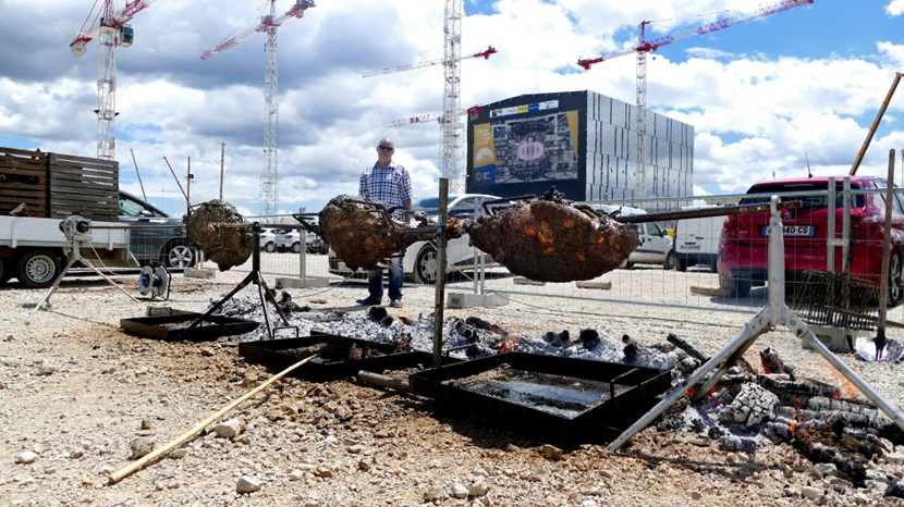 150 kilos of bull meat slowly roast over the fire, with the ITER Assembly Hall in the background. (Click to view larger version...)
