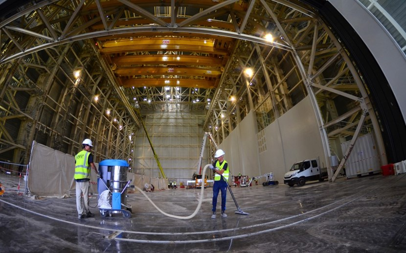 In the 60-metre-tall building for pre-assembly activities, workers go over the painted surface of the basemat. Later, when construction activities on the Tokamak Building are finalized, the temporary wall seen at the end of the building will come down and the cranes will operate along a 170-metre crane bay. The double building will operated as a clean space during the assembly of the machine. (Click to view larger version...)