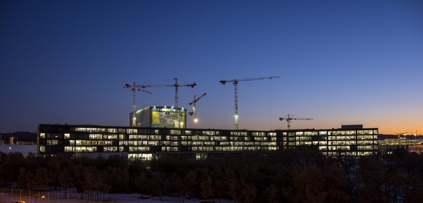 Behind the lit offices of the ITER Headquarters building, with desks for 800 people, the scientific installation is rising. (Click to view larger version...)