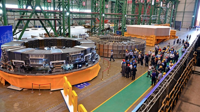 Ten metres in diameter, 1.2 metres in height, and with a cross-section of 1.6 metres: poloidal field coil #6 will be installed under the machine inside of the cryostat base. After six years of fabrication, the coil is ready to be shipped to ITER. (To the right of the completed component is the vacuum chamber where high-voltage tests were carried out and—further along—the transport case on the transport frame.) (Click to view larger version...)