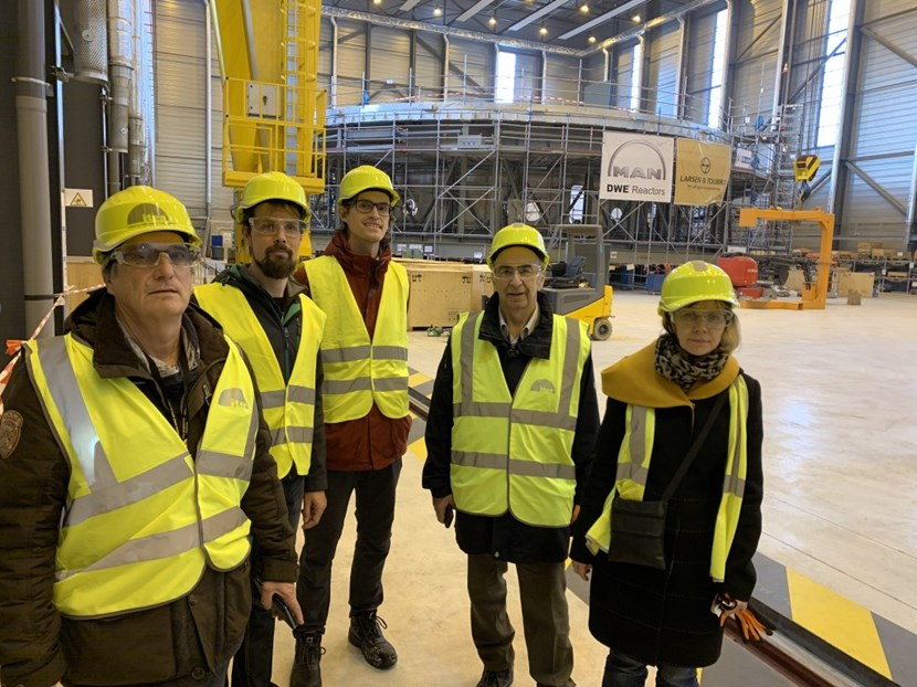 During a meeting at ITER, Scientist Fellows from the Divertor and SOL simulation group tour the Cryostat Workshop. In the background: the 1,250-tonne cryostat base that is being readied for transfer to the Tokamak pit. (Click to view larger version...)
