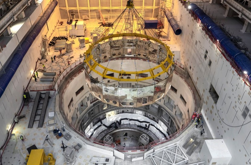 The component has travelled the whole length of the assembly theatre and is now positioned right above the pit. Two alignment tools, visible at the bottom of the large circular opening, will guide its final trajectory. (Click to view larger version...)