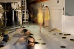 Tungsten atoms (dancers in black) in the fusion reactor wall get displaced by neutrons from the fusion reaction, and go on to displace neighbouring tungsten atoms in a knock-on effect. The defects in the metal lattice then capture hydrogen (yellow).
