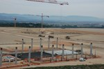 The columns for the Poloidal Field Coil Fabrication Building are rising out the ground in the foreground, while the Tokamak pit is taking shape in the background.